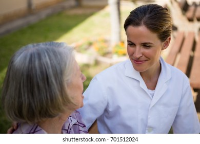 High angle view of doctor talking to senior woman while sitting on bench in yard