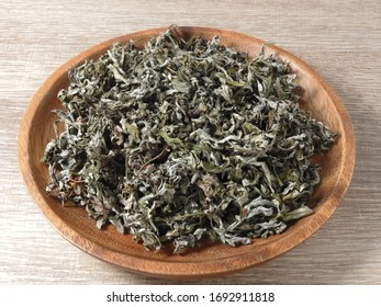 High angle view of dry mugwort on wooden plate. Chinese medicine. During the Dragon Boat Festival, is usually hung on the door, which is used to ward off evil spirits and to drive away mosquitoes.