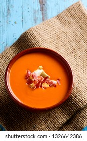 high angle view of an earthenware bowl with spanish salmorejo cordobes or porra antequerana, a cold tomato soup topped with serrano ham and croutons, on a blue rustic table