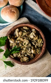 high angle view of an earthenware plate with some sliced mushrooms cooked with garlic and parsley, on a wooden tray placed on a gray rustic wooden table next to a plate with some bread buns