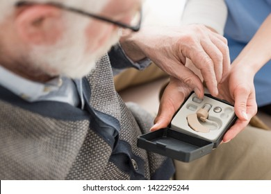 High angle view of elderly man looking at box with hearing aid
