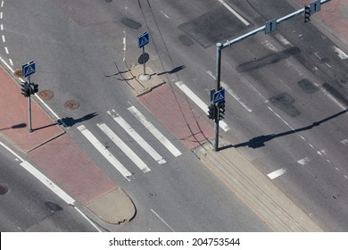 high angle view of an empty street intersection with cross walk markings, traffic signal lights