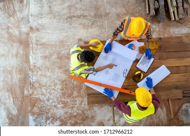 High angle view of engineer and architect discussing building plan at construction site,Group of builders having conversation about building plan.