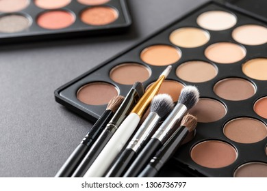 High angle view of an eyeshadow palette and an eyelid make up brushes collection