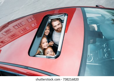 high angle view of family looking out of sunroof of car