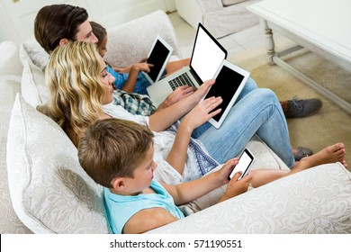 High angle view of family using various technologies while sitting on sofa