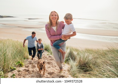 High angle view of family walking up a sand dune at the beach.