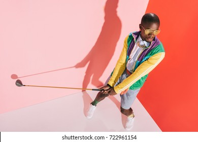 high angle view of fashionable african american man in sunglasses playing golf in studio