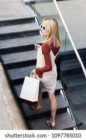high angle view of fashionable blonde woman in sunglasses holding paper bags on stairs
