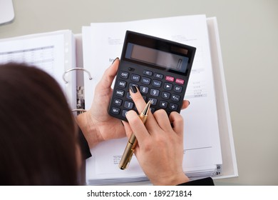 High angle view of female accountant calculating tax at desk in office