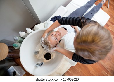 High angle view of female beautician washing customer's hair with shampoo at beauty salon