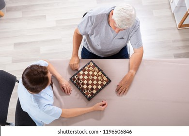 High Angle View Of Female Caretaker Playing Chess With Senior Man On Desk