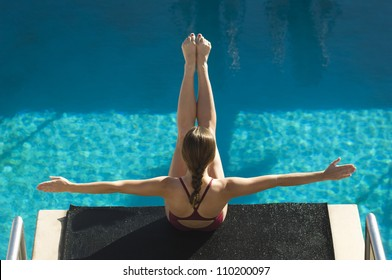 High angle view of a female diver on diving board with arms out