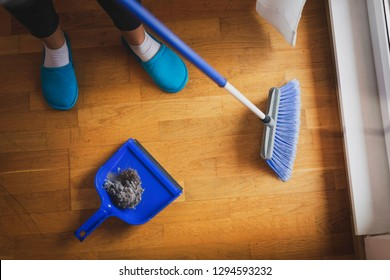 High angle view of female hands holding a broom and sweeping floor, collecting dust onto a dustpan. Focus on the dust in a dustpan and the broom