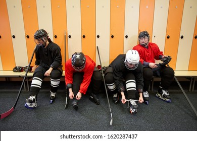 High angle view at female hockey team putting on gear in locker room while preparing for match or practice, copy space