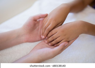High angle view of female therapist examining hands on white towel