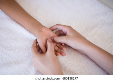 High angle view of female therapist massaging palm on white towel at hospital ward