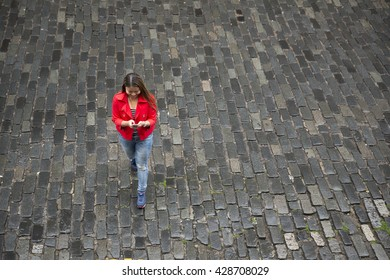 A high angle view of a Filipino woman using her Smart Phone outdoors on a city street.