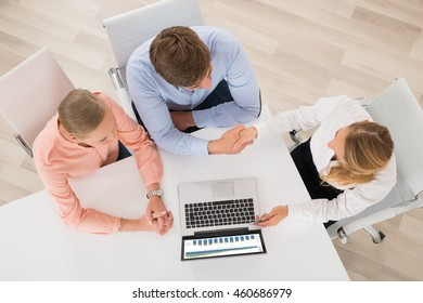 High Angle View Of Financial Advisor Shaking Hands With Couple In Office