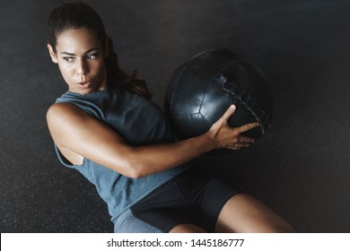 High angle view focused motivated strong woman workout sitting gym floor, breathing determined, training crunch abs holding medicine ball. Athletic sportswoman perform crossfit fitness exercise