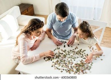 high angle view of focused parents and daughter playing with puzzles