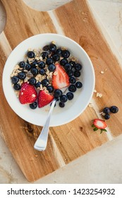 HIgh angle view of a fresh healthy breakfast. There is fresh fruit, oats and milk in a bowl with a spoon. The bowl is placed on a wooden chopping board.