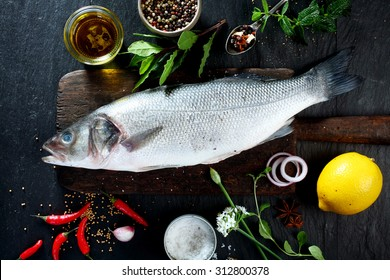 High Angle View of Fresh Raw Whole Fish on Rustic Wooden Cutting Board Surrounded by Fresh Herbs and Spices for Seasoning and Garnishing