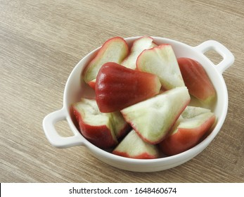 High angle view of fresh sliced wax apple (also called rose apple) on plate on wooden background.  Fruit and agriculture concept. Taiwan fruit produced in Kaohsiung.  With copy space.