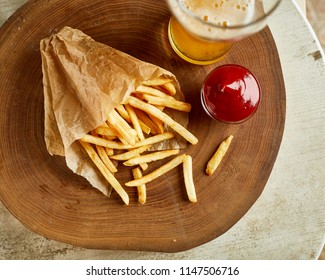 High angle view of fried french potato, served on wood with glass of beer and ketchup. Fast food