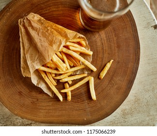 High angle view of fried french potato, served on wood with glass of beer. Fast food