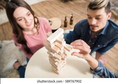 high angle view of friends playing jenga game at home