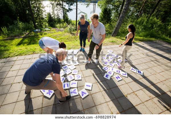 High Angle View Of Friends Solving Crossword Puzzle On Patio
