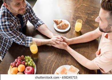 High angle view of gay couple holding hands holding hands and looking at each other while having breakfast
