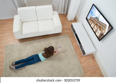 High Angle View Of Girl Lying On Carpet Watching Television At Home