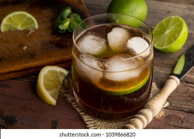 High angle view of a glass of Cuba Libre cocktail with rum, coke, lemon juice and ice cubes on a rustic wooden table. Focus on the ice