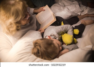High angle view  of grandmother wearing glasses reading bedtime stories to sleeping little boy in dark room under lamplight