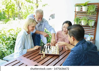 high angle view of a group of multiethnic senior people playing chess board with happy smiling face on sunny day