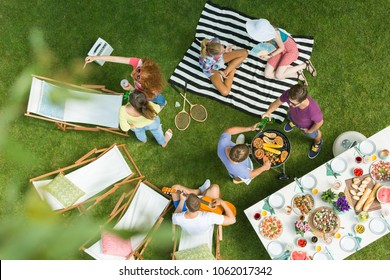 High angle view of group of people having backyard barbecue party with grill, guitar, deck chairs and delicious food on the table