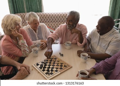 High angle view of group of senior people playing chess on table in living room at nursing home