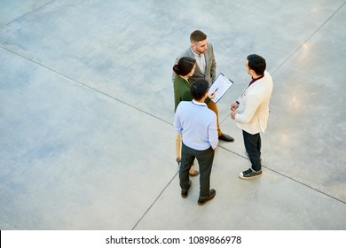 High angle view at group of successful young business people standing in circle discussing project in modern office building, copy space