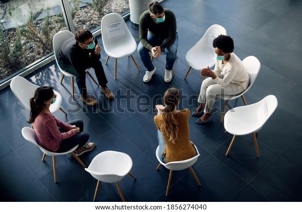 Vista en ángulo alto de los participantes en terapia de grupo sentados en círculo y hablando mientras usan máscaras protectoras de cara debido a la pandemia COVID-19.