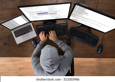 High Angle View Of Hacker Stealing Information From Computers At Desk