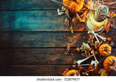 High angle view of halloween pumpkins with bones and vintage lamp under spider web against wooden background