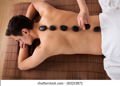 High angle view of hand placing lastone on man's back in spa