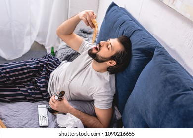 high angle view of handsome loner eating pizza and holding bottle of beer in bedroom
