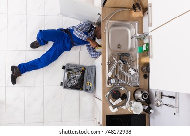 High Angle View Of Handyman Lying On Floor Repairing Sink In Kitchen With Toolbox