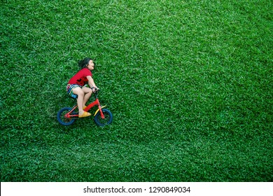 High Angle View of a Happy Asian Kids. Girl on Bicycle Lay Down at Green lawn in Summer Day. Excited Asian Children in Outdoor Park
