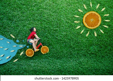 High Angle View of a Happy Asian Kids. Girl on Bicycle Lay Down at Green lawn in Summer Sunny Day. Imagination and Creativity Children in Outdoor Park