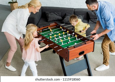 high angle view of happy family with two kids playing table football together at home