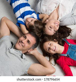 High Angle View Of Happy Family With Two Children Lying On Floor